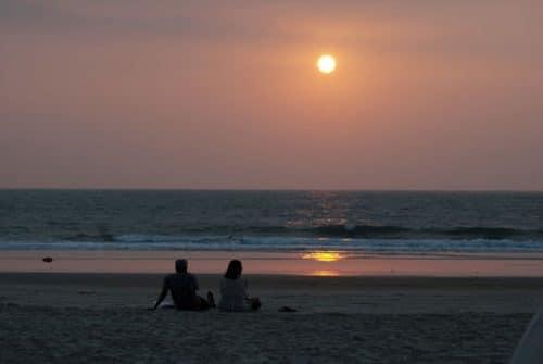 砂浜で夕陽を眺めるカップル